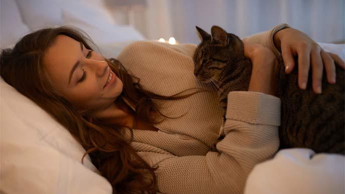 猫と温めあう女性