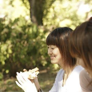サンドイッチでランチ代を節約する女性