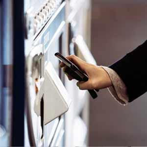 iDを使って自販機で缶コーヒーを買う女性