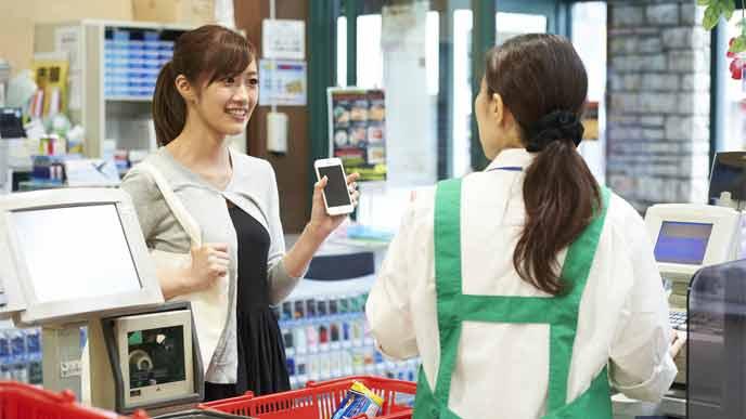 スーパーのレジでiDおサイフケータイで支払いする女性