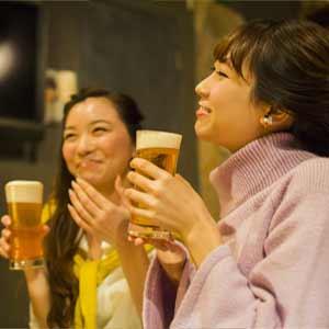 居酒屋で株主優待を満喫する女性