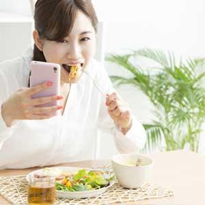 ご飯を食べながらアンケートサイトでポイントを稼ぐ女性