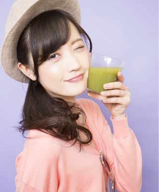 高い野菜の代わりに野菜ジュースを飲む女性