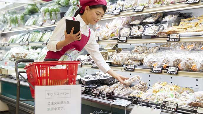 新鮮な野菜を集めるネットスーパーの店員