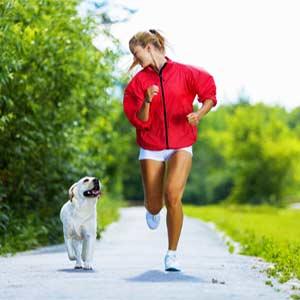 Apple Watchをつけて犬とジョギングする女性