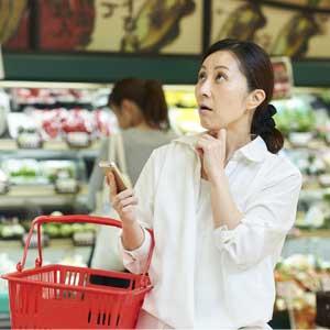 スーパーで節約する主婦