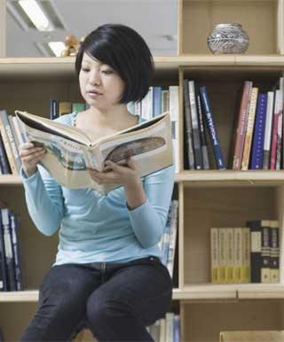 図書館で専門書を楽しむ女性