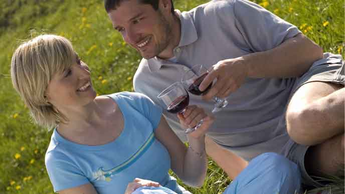 芝生でピクニックデートするカップル