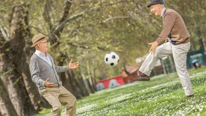 公園でサッカーを楽しむアクティブなおじいさん