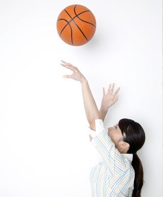 お金をかけずにバスケットボールをする女性