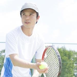 公園のテニスコートで安くテニスを楽しむ男性
